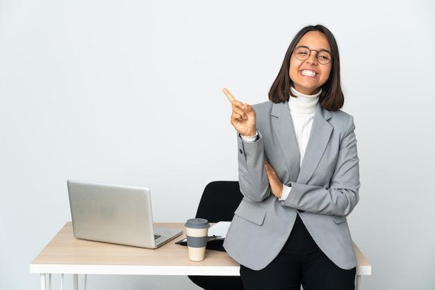 Jovem mulher de negócios latinos trabalhando em um escritório isolado no branco mostrando e levantando um dedo em sinal dos melhores