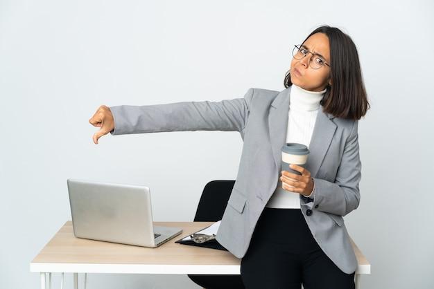 Jovem mulher de negócios latinos trabalhando em um escritório isolado no branco, mostrando o polegar para baixo com expressão negativa
