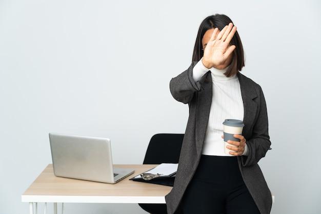 Jovem mulher de negócios latinos trabalhando em um escritório isolado no branco na posição traseira