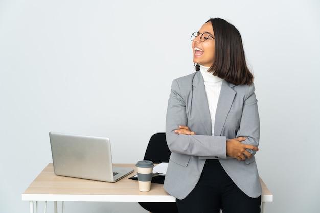 Jovem mulher de negócios latinos trabalhando em um escritório isolado no branco rindo em posição lateral