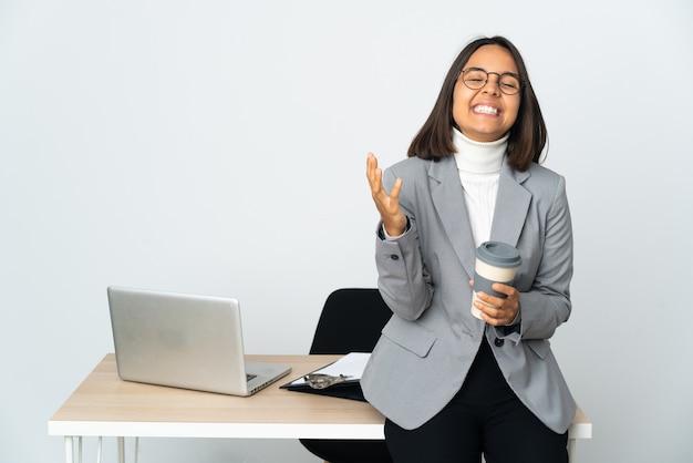 Jovem mulher de negócios latinos trabalhando em um escritório isolado no branco sorrindo muito