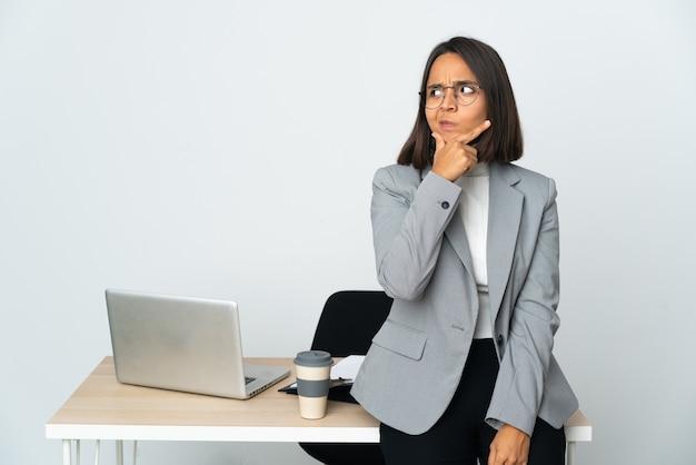 Jovem mulher de negócios latinos trabalhando em um escritório isolado no branco tendo dúvidas