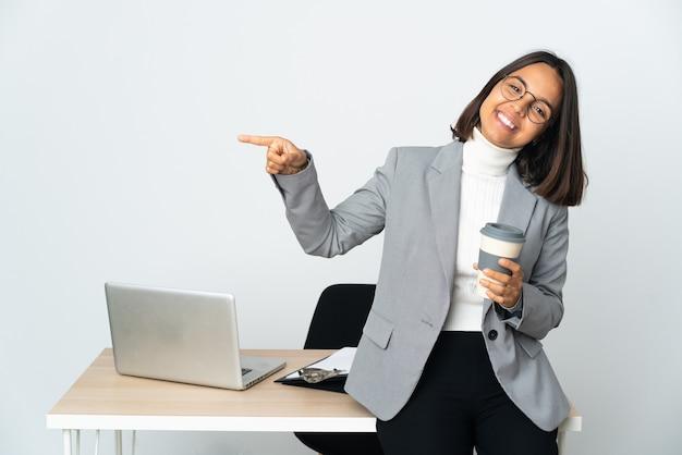 Jovem mulher de negócios latinos trabalhando em um escritório isolado no fundo branco apontando o dedo para o lado e apresentando um produto