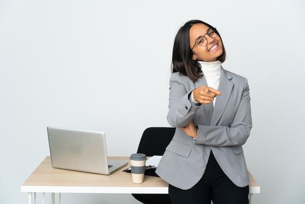 Jovem mulher de negócios latinos trabalhando em um escritório isolado no fundo branco apontando para a frente com uma expressão feliz