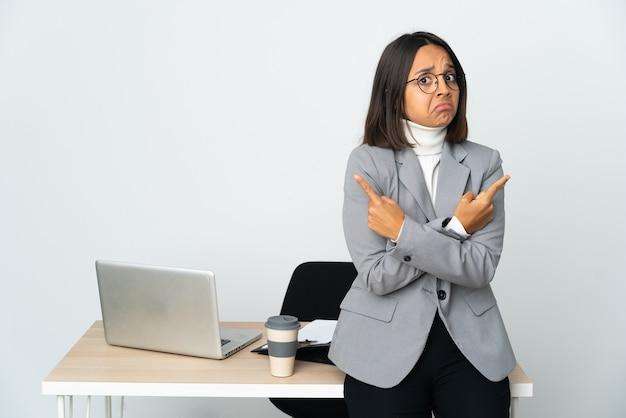 Jovem mulher de negócios latinos trabalhando em um escritório isolado no fundo branco apontando para as laterais tendo dúvidas