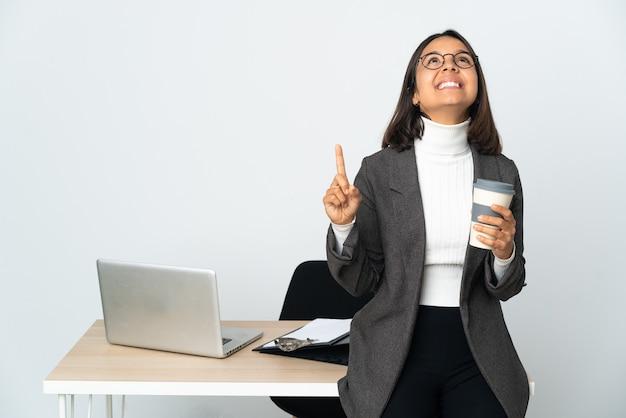 Jovem mulher de negócios latinos trabalhando em um escritório isolado no fundo branco apontando para cima e surpreso