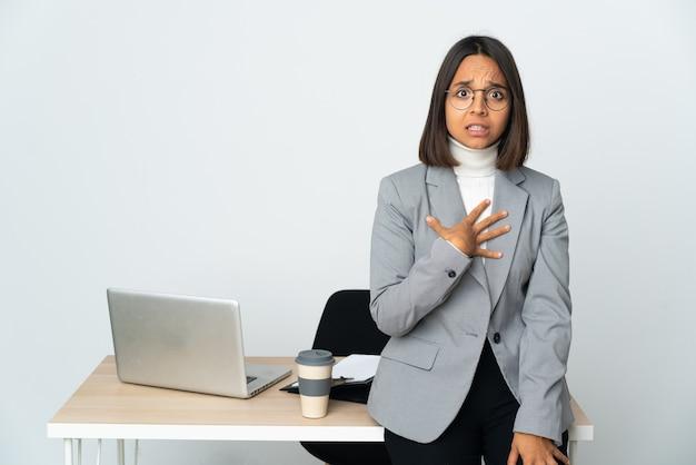 Jovem mulher de negócios latinos trabalhando em um escritório isolado no fundo branco apontando para si mesma