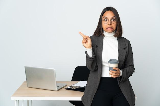 Jovem mulher de negócios latinos trabalhando em um escritório isolado no fundo branco assustada e apontando para o lado