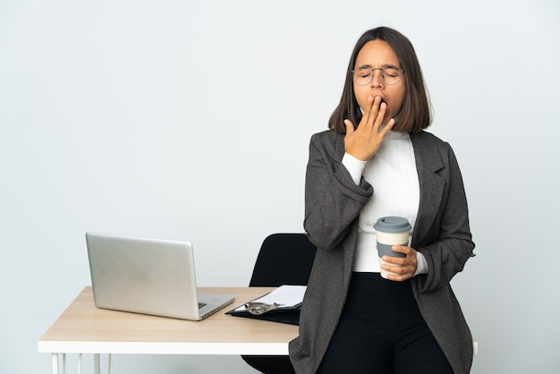 Jovem mulher de negócios latinos trabalhando em um escritório isolado no fundo branco, bocejando e cobrindo a boca aberta com a mão