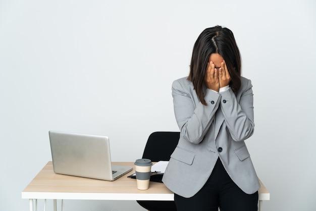 Jovem mulher de negócios latinos trabalhando em um escritório isolado no fundo branco com expressão de cansaço e doentia.
