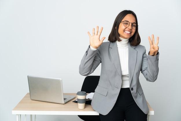 Jovem mulher de negócios latinos trabalhando em um escritório isolado no fundo branco, contando oito com os dedos