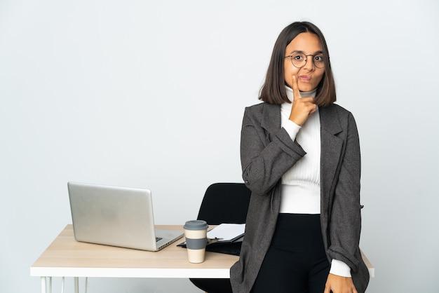 Jovem mulher de negócios latinos trabalhando em um escritório isolado no fundo branco e pensando