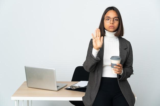 Jovem mulher de negócios latinos trabalhando em um escritório isolado no fundo branco fazendo gesto de pare