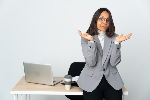 Jovem mulher de negócios latinos trabalhando em um escritório isolado no fundo branco fazendo gestos de dúvidas