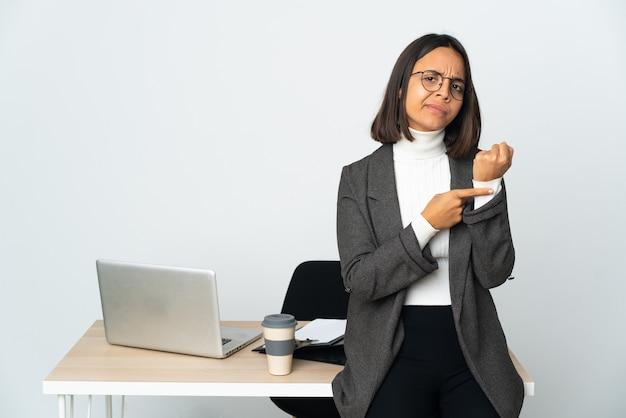 Jovem mulher de negócios latinos trabalhando em um escritório isolado no fundo branco fazendo o gesto de estar atrasado