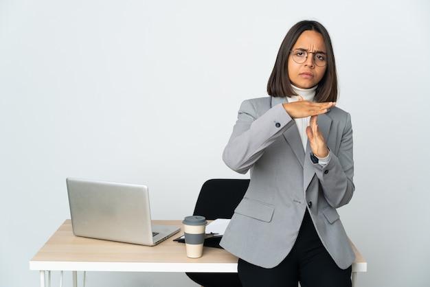 Jovem mulher de negócios latinos trabalhando em um escritório isolado no fundo branco, fazendo um gesto de castigo
