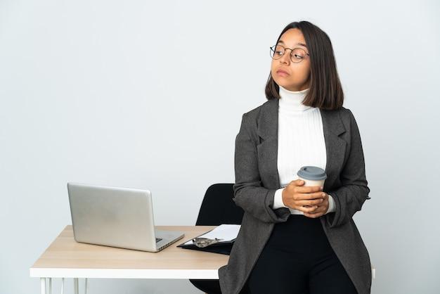 Jovem mulher de negócios latinos trabalhando em um escritório isolado no fundo branco fazendo um gesto de dúvida olhando para o lado