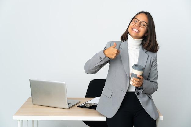 Jovem mulher de negócios latinos trabalhando em um escritório isolado no fundo branco fazendo um gesto de polegar para cima