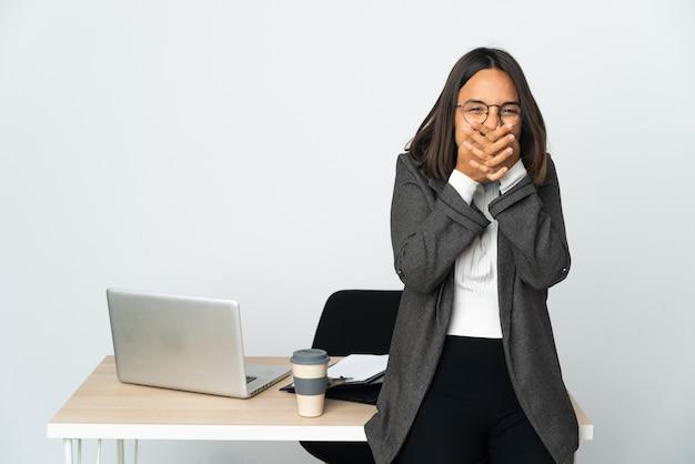 Jovem mulher de negócios latinos trabalhando em um escritório isolado no fundo branco feliz e sorridente cobrindo a boca com as mãos