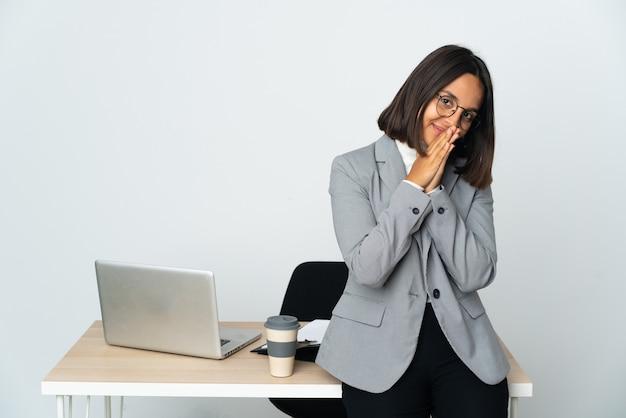 Jovem mulher de negócios latinos trabalhando em um escritório isolado no fundo branco mantém as palmas das mãos juntas. pessoa pede algo