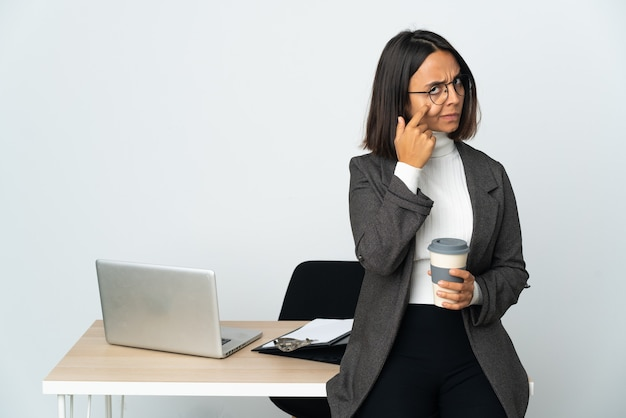 Jovem mulher de negócios latinos trabalhando em um escritório isolado no fundo branco mostrando algo