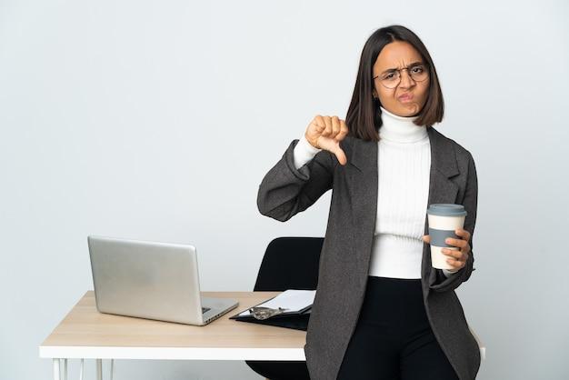 Jovem mulher de negócios latinos trabalhando em um escritório isolado no fundo branco, mostrando o polegar para baixo com expressão negativa