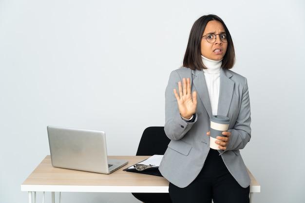 Jovem mulher de negócios latinos trabalhando em um escritório isolado no fundo branco, nervosa, esticando as mãos para a frente