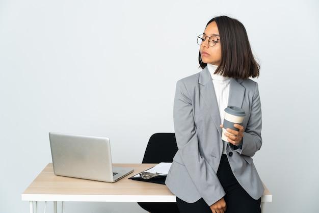 Jovem mulher de negócios latinos trabalhando em um escritório isolado no fundo branco, olhando para o lado