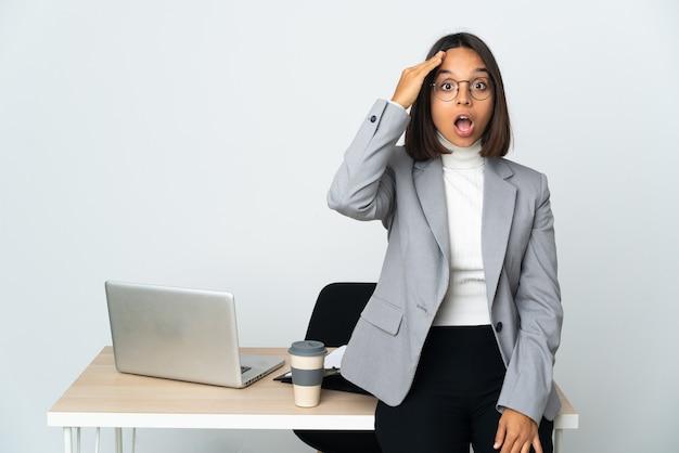 Jovem mulher de negócios latinos trabalhando em um escritório isolado no fundo branco percebeu algo e pretende a solução