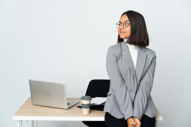 Jovem mulher de negócios latinos trabalhando em um escritório isolado no fundo branco. retrato