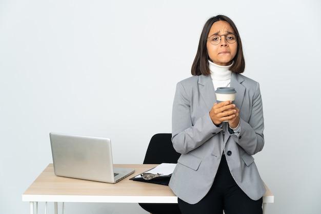 Jovem mulher de negócios latinos trabalhando em um escritório isolado no fundo branco rindo