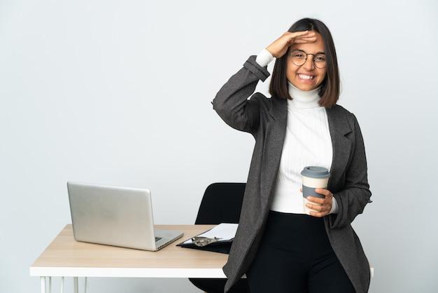 Jovem mulher de negócios latinos trabalhando em um escritório isolado no fundo branco, saudando com a mão com expressão feliz