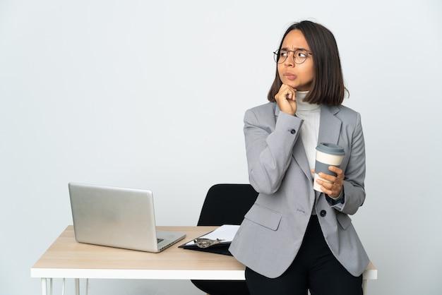 Jovem mulher de negócios latinos trabalhando em um escritório isolado no fundo branco, tendo dúvidas e pensando