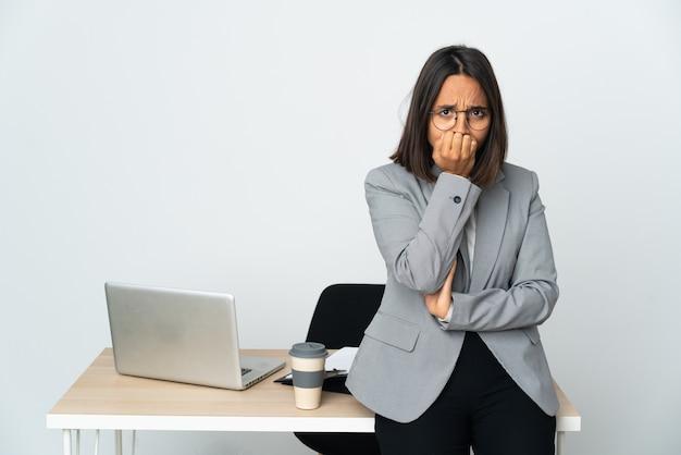 Jovem mulher de negócios latinos trabalhando em um escritório isolado no fundo branco, tendo dúvidas