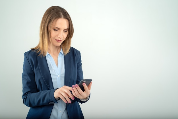 Jovem mulher de negócios lê notícias em um celular isolado em fundo cinza