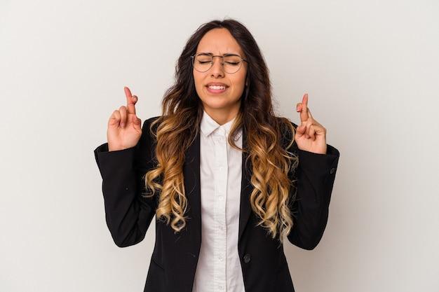 Jovem mulher de negócios mexicana isolada no fundo branco cruzando os dedos para ter sorte