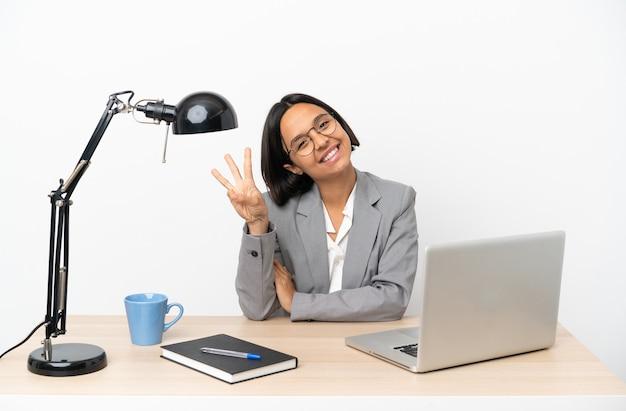 Jovem mulher de negócios misturados a trabalhar num escritório feliz e a contar três com os dedos