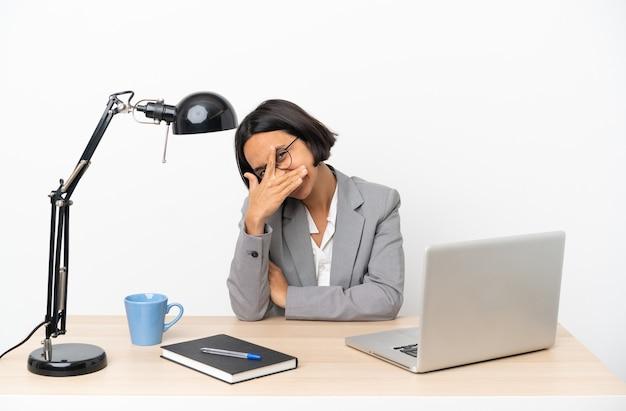 Jovem mulher de negócios misturados trabalhando no escritório cobrindo os olhos pelas mãos e sorrindo