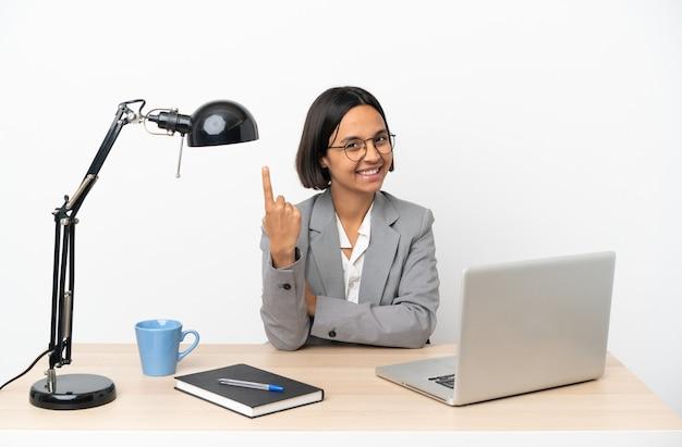 Jovem mulher de negócios misturados trabalhando no escritório fazendo gesto de vir.