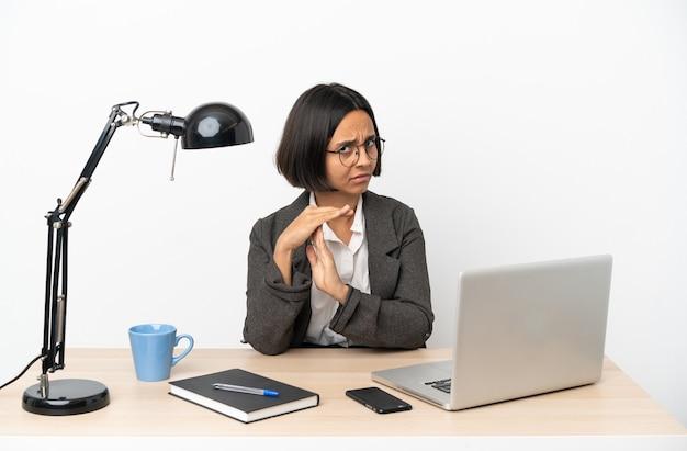 Jovem mulher de negócios misturados trabalhando no escritório fazendo um gesto de castigo