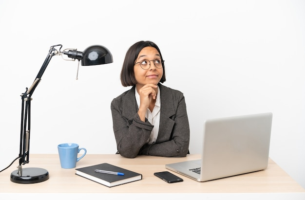 Jovem mulher de negócios misturados trabalhando no escritório pensando em uma ideia enquanto olha para cima