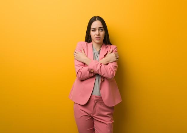 Jovem mulher de negócios moderna ficando fria devido à baixa temperatura
