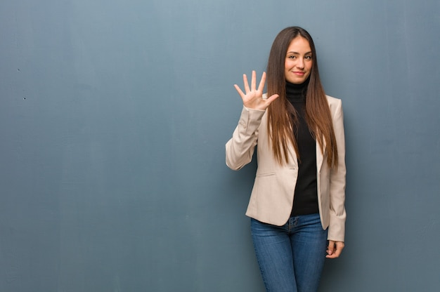 Jovem mulher de negócios mostrando o número cinco