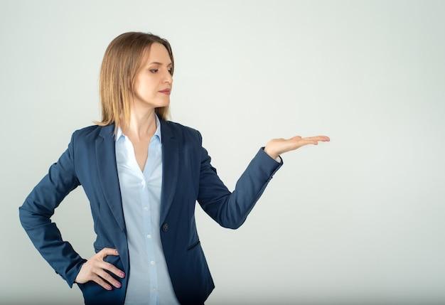 Jovem mulher de negócios mostrando um espaço vazio isolado em um fundo cinza