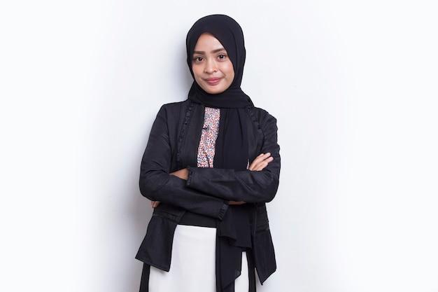 Jovem mulher de negócios muçulmana asiática com lenço na cabeça sorrindo com os braços cruzados no fundo branco