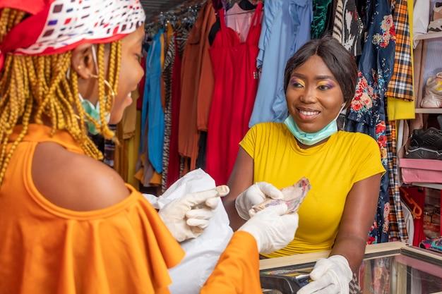 Jovem mulher de negócios na áfrica recebendo dinheiro de um cliente