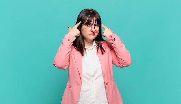 Jovem mulher de negócios olhando concentrada e pensando seriamente em uma ideia, imaginando uma solução para um desafio ou problema
