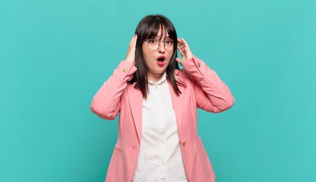 Jovem mulher de negócios parecendo animada e surpresa, boquiaberta e com as duas mãos na cabeça, sentindo-se uma sortuda vencedora