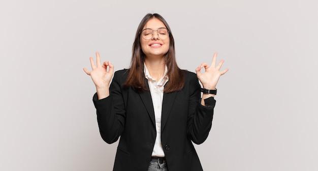 Jovem mulher de negócios parecendo concentrada e meditando, sentindo-se satisfeita e relaxada, pensando ou fazendo uma escolha