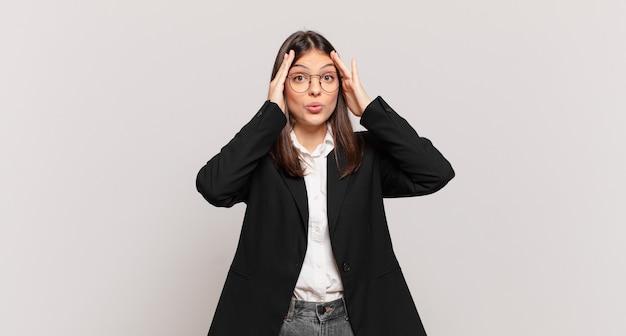 Jovem mulher de negócios parecendo desagradavelmente chocada, assustada ou preocupada, com a boca bem aberta e cobrindo as duas orelhas com as mãos